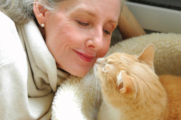Mature female beauty interacting with her cat.