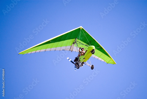 Airborne Motorized Ultralight Glider in a cloudless blue sky - 5148664