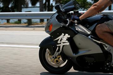 man riding silver superbike at speed