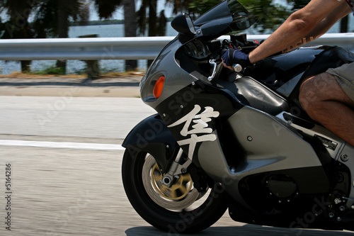 man riding silver superbike at speed