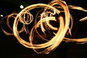 Poi dance performance with fire circular patterns
