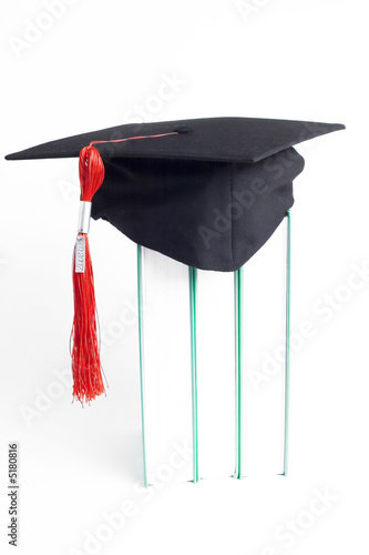 graduation cap with a red tassel on books on white background