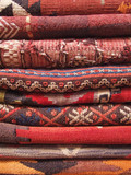 Red turkish carpets stacked in a traditional store poster