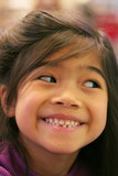 Seven year old girl proudly showing her loose tooth. poster