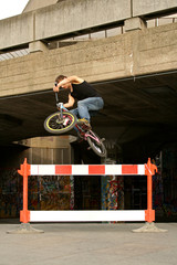 young bmx stunt rider with graffiti background