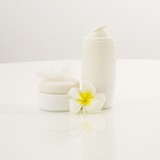 Facial skin cream bottles over white with tropical flower poster