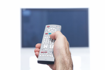 Hand with remote control and flat tv