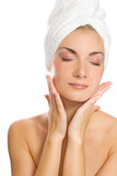 Young lovely lady applying moisturizer to her face after shower poster