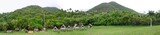 Tropical panorama with hills and rustic cabins