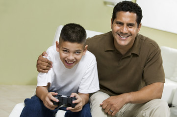 Father with Son Playing Video Game on sofa in living room, portrait