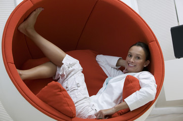 Woman Sitting Inside of Egg Chair