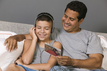 Father and Son listening to Music sitting on bed
