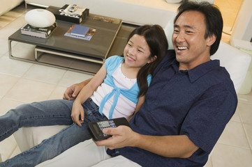 Father and Daughter Watching TV Together in living room, high angle view