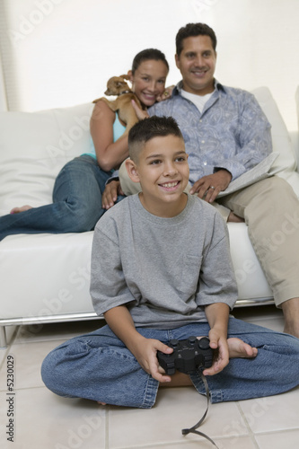 Parents Watching Son Play Video Games in living room, front view