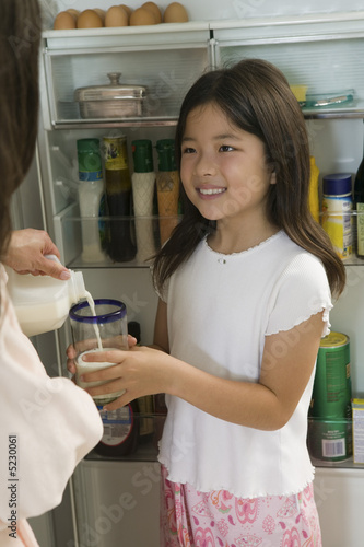 Mother Pouring Milk For Daughter in kitchen by open fridge, close up of daughter