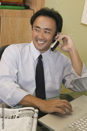 Businessman Using Cell Phone and Laptop