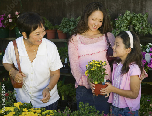 Grandmother, mother and daughter Shopping for Plants in nursery