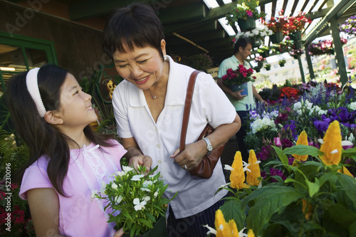 Grandmother and granddaughter in plant nursery