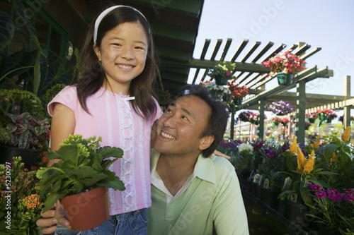 Father and Daughter in plant nursery, portrait, close up
