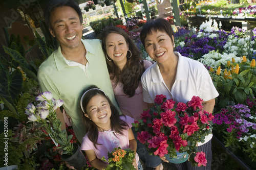 Family holding plants in nursery, portrait, high angle view