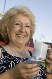 Senior Woman outdoors, listening to portable music player, holding cup, smiling.