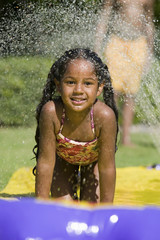 Girl 5-9 Sliding on water slide, portrait.