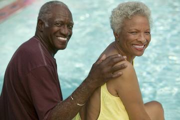 Senior Couple sitting by swimming pool, portrait.