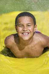 Boy 7-9 sliding on water slide, front view portrait.