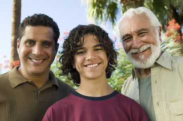 Boy 13-15 with Father and Grandfather outdoors, front view portrait.