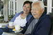 Senior couple drinking tea on porch, smiling