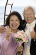 Couple at wedding giving thumbs-up, smiling, portrait