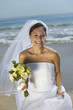 Bride with bouquet on beach, smiling, portrait