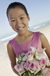 Young Bridesmaid with flowers on beach, portrait