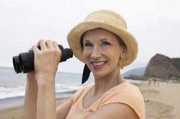 Woman using binoculars at beach, portrait