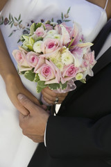 Bride and Groom holding hands and bouquet, close-up