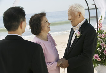 Groom with parents at beach wedding