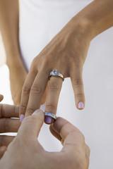 Groom putting wedding ring on brides finger, close-up