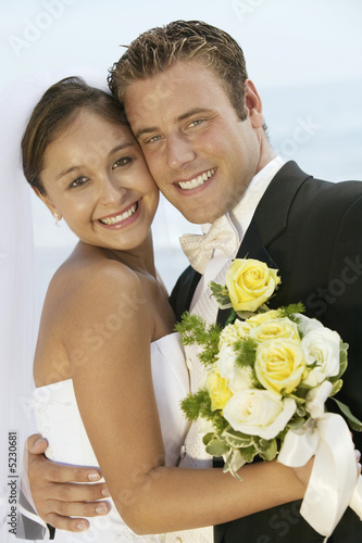 Bride and Groom Hugging on Beach