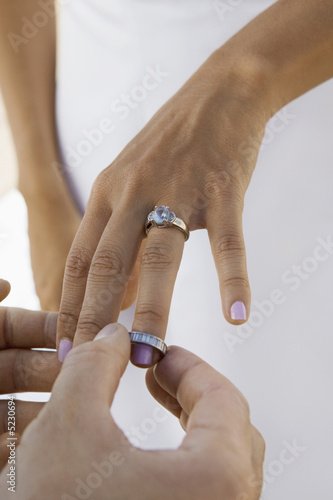 Groom putting wedding ring on brides finger, close-up