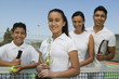 Tennis Family on court by net, daughter holding trophy, portrait