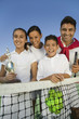 Tennis Family at net on tennis court, daughter holding trophy, portrait