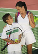 Mother and son by net on tennis court, high angle view
