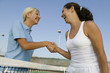 Two female Tennis Players shaking hand over tennis court net, low angle view