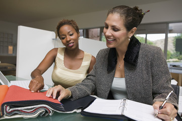 Two women with laptop and organizer examining fabric swatches