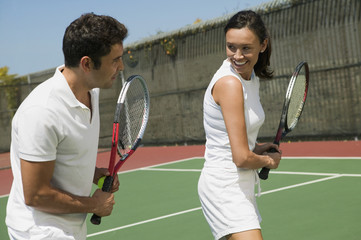 Woman and male tennis instructor practising racket control on tennis court