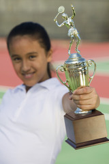 Young girl on tennis court holding trophy, focus on trophy
