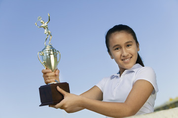 Young girl at net on tennis court holding trophy, portrait, low angle view