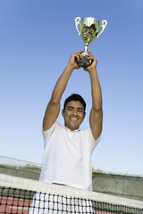 Tennis Player on court by net Holding Trophy Over Head, portrait