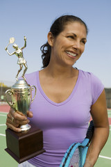 Mid-adult female tennis player on court holding trophy, front view