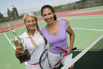 Two female Tennis Players by net on court holding trophy, portrait